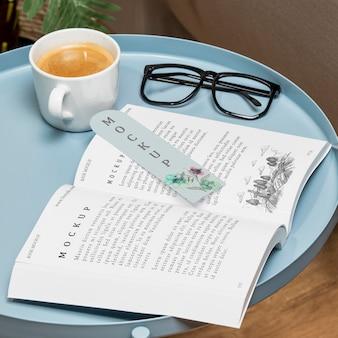 Maquette de livre ouvert à angle élevé sur table basse avec des lunettes