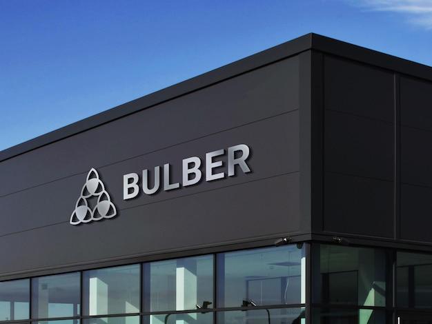 Maquette de logo 3d chrome sur une façade de bâtiment noire