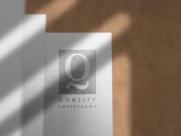 Maquette de logo en argent gravé sur papier lin
