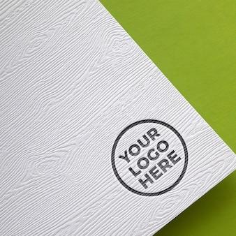 Maquette de logo effet de gravure sur papier en bois sur la texture de fond vert