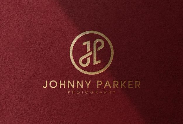 Maquette de logo de feuille d'or de luxe sur papier texturé rouge