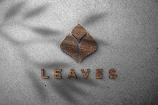 Maquette de logo de feuilles - effet en bois de maquette de logo 3d sur un mur blanc