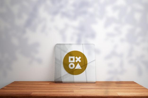 Maquette de logo or sur verre sur table en bois