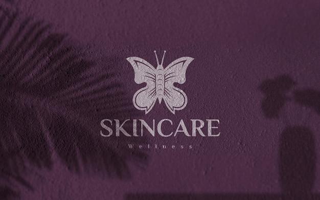 Maquette de logo peint en blanc sur un mur violet