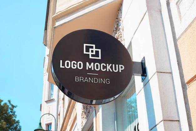 Maquette de logo sur une plaque de rue ronde au-dessus du magasin. signalisation moderne et noire