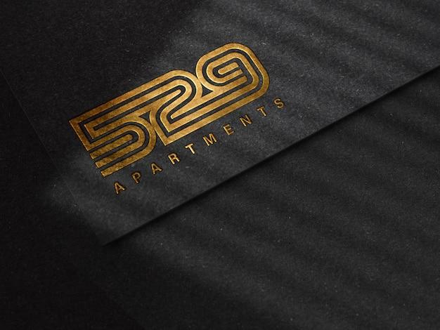 Maquette de logo en relief de luxe sur la texture du papier noir