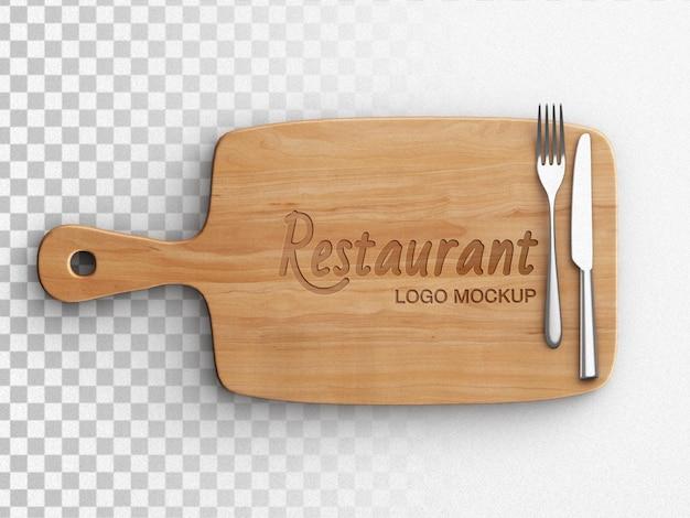 Maquette de logo de restaurant sur un concept de cuisine de planche à découper en bois avec vaisselle plate isolée