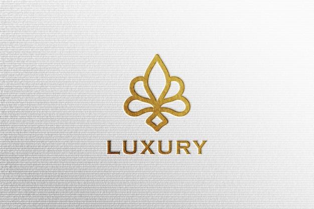 Maquette de logo simple de luxe en feuille d'or sur papier pressé blanc
