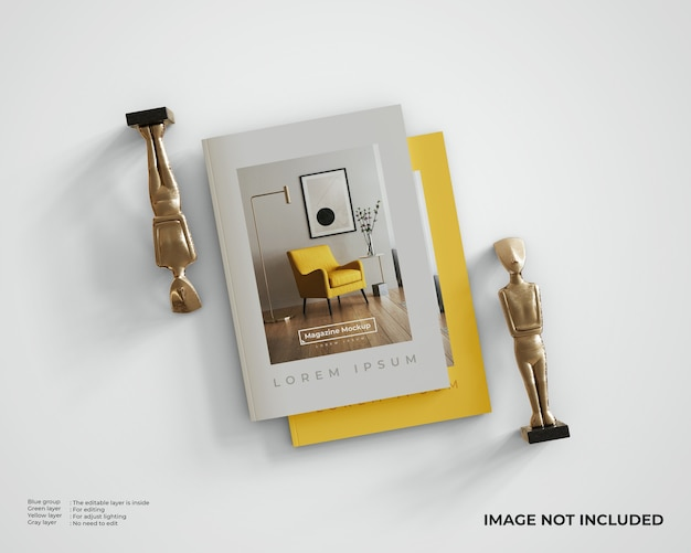 Maquette de magazine empilée avec deux statues. vue de dessus