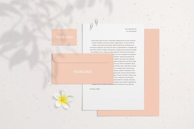 Maquette de marque vierge de l'été avec des cartes de visite corail, enveloppes sur un mur lumineux avec fleur et ombres. la couche intelligente psd peut se déplacer. papeterie
