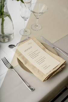 Maquette de menu de printemps à angle élevé sur assiette avec couverts et verres