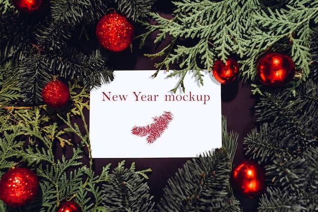 Maquette de noël, feuille de papier blanc posé sur des branches d'épinette, boules de noël rouges.
