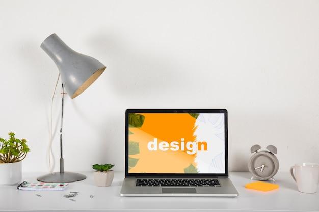 Maquette d'ordinateur portable sur le bureau avec des éléments