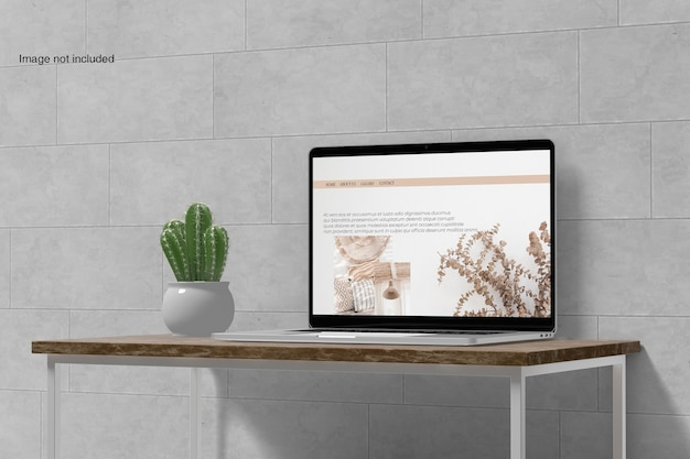 Maquette d'ordinateur portable sur le bureau avec fleur de cactus