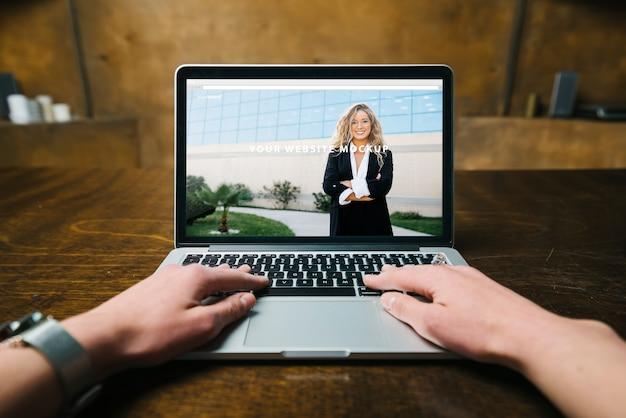 Maquette d'ordinateur portable avec les mains