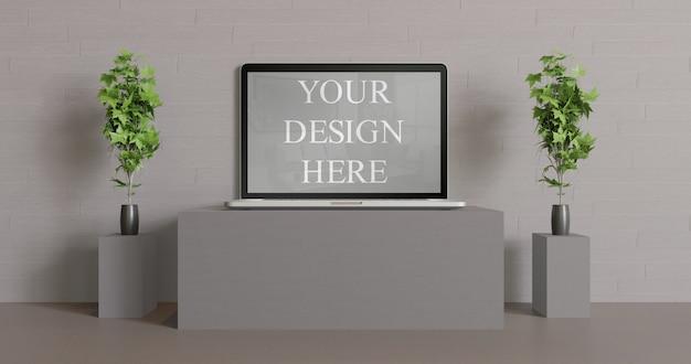 Maquette d'ordinateur portable vue de face sur la table noire avec quelques plantes vas