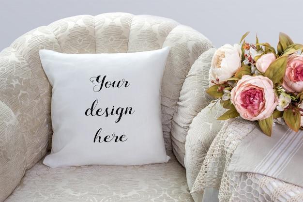 Maquette d'oreiller blanc, coussin sur un fauteuil avec des fleurs