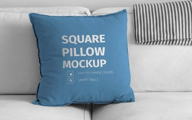 Maquette d'oreiller carré sur canapé blanc