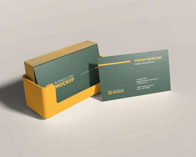 Maquette de papeterie empilée carte de visite dans une boîte jaune
