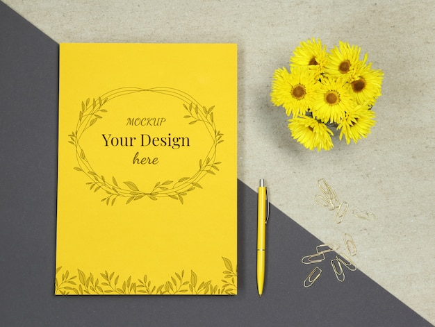 Maquette en papier jaune avec fleurs, stylo et pinces dorées