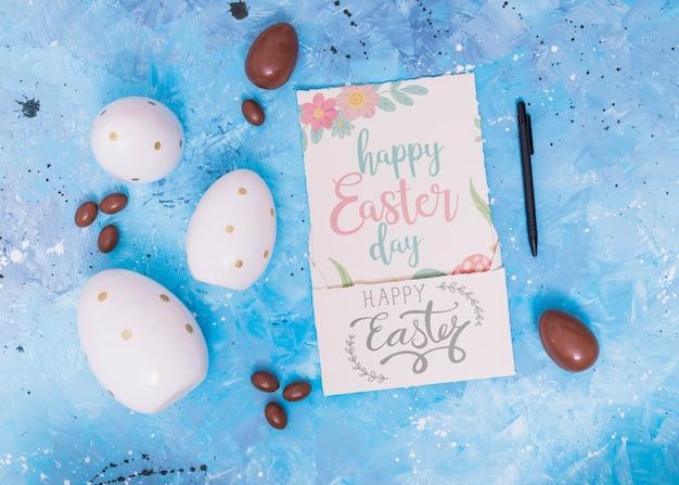 Maquette de pâques avec une carte et des œufs en chocolat