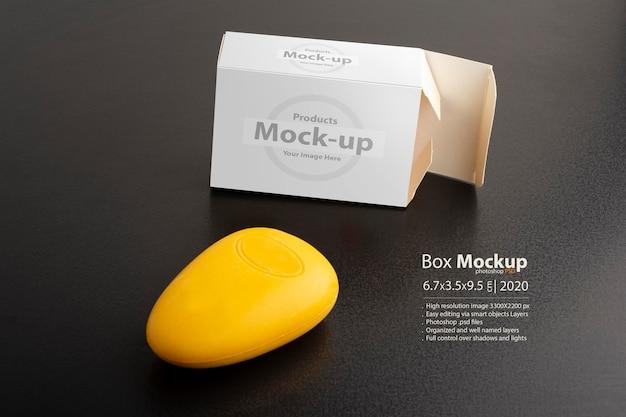 Maquette de paquet de savon jaune ouvert sur une surface noire