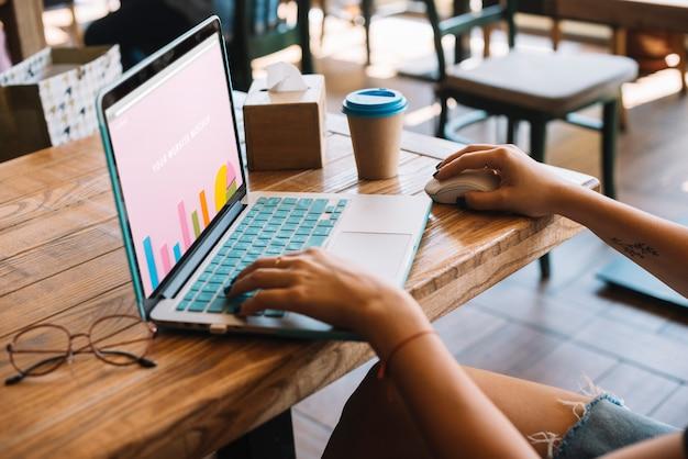 Maquette pour ordinateur portable avec femme sur une table en bois