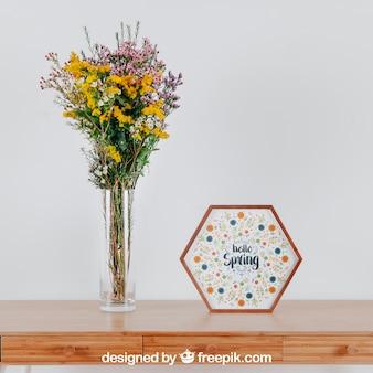 Maquette de printemps avec cadre hexagonal et vase de fleurs sur la table