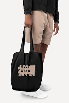 Maquette psd de sac fourre-tout noir avec prise de vue en studio d'accessoires de typographie battre vos peurs