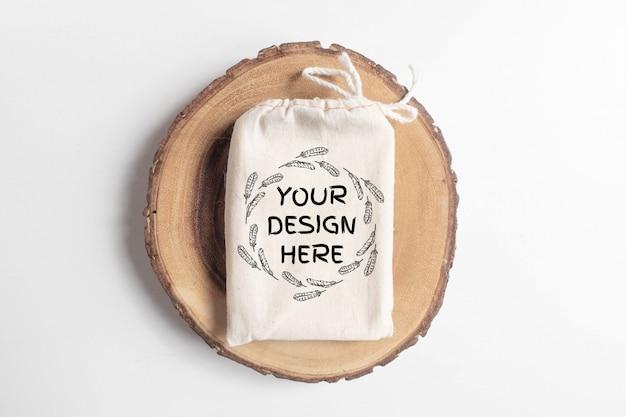 Maquette de sac en coton sur un arbre coupé en bois