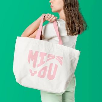 Maquette de sac fourre-tout beige psd avec la typographie rose miss you