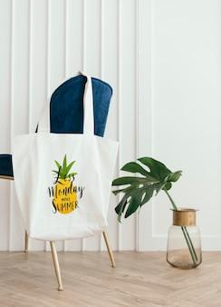 Maquette de sac fourre-tout blanc accroché à une chaise en velours bleu