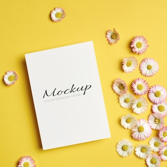 Maquette de salutation ou d'invitation ou de carte avec des fleurs de marguerite sur jaune
