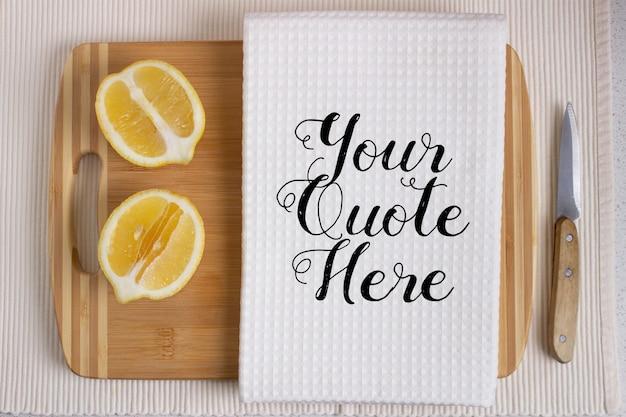 Maquette d'une serviette de cuisine blanche sur une planche à découper en bois avec des citrons frais