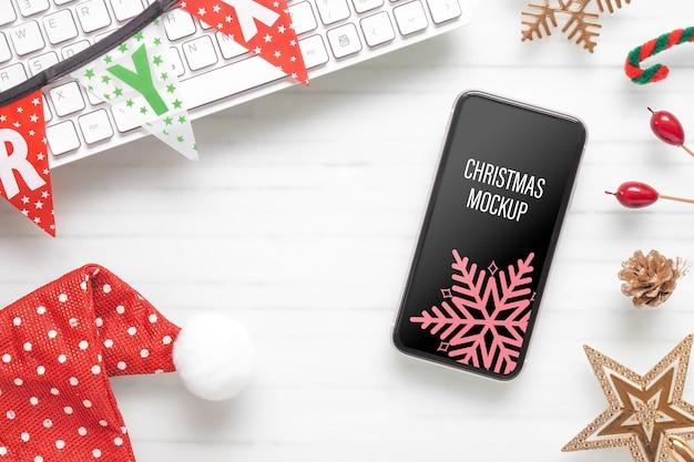 Maquette smartphone sur le bureau à domicile pour la fête de noël et du nouvel an