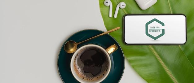 Maquette de smartphone, écouteur sans fil et tasse à café