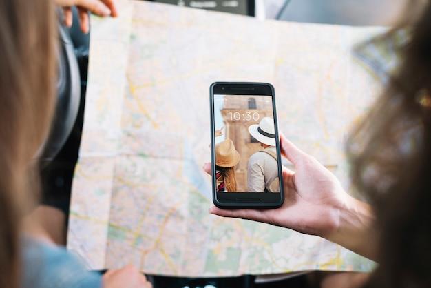 Maquette de smartphone avec des filles regardant la carte