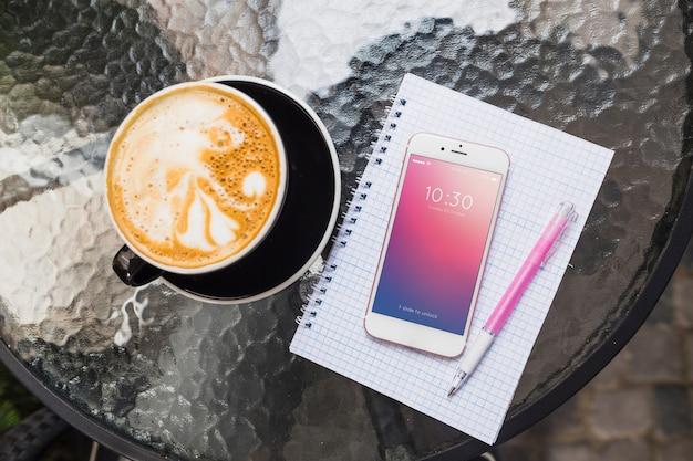 Maquette de smartphone sur table avec cappuchino