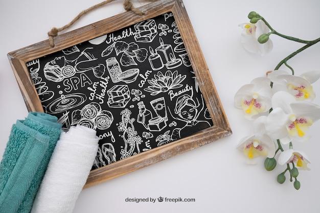 Maquette de spa avec ardoise, serviettes et fleurs