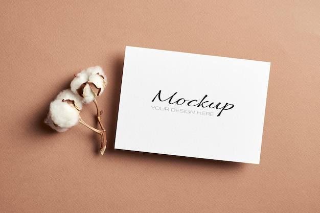 Maquette stationnaire de carte d'invitation ou de dépliant avec des fleurs de coton naturel sec sur beige