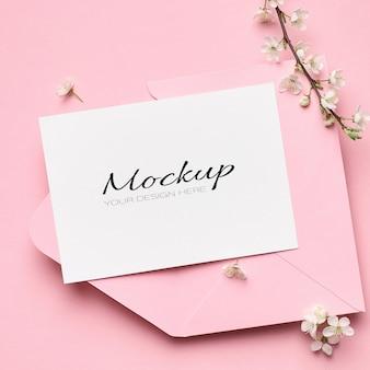 Maquette stationnaire de carte de voeux avec enveloppe et branches de cerisier de printemps sur rose