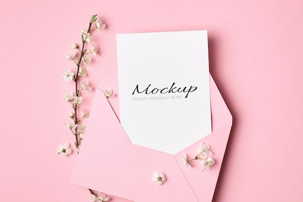 Maquette stationnaire de carte de voeux avec enveloppe et branches de cerisier de printemps