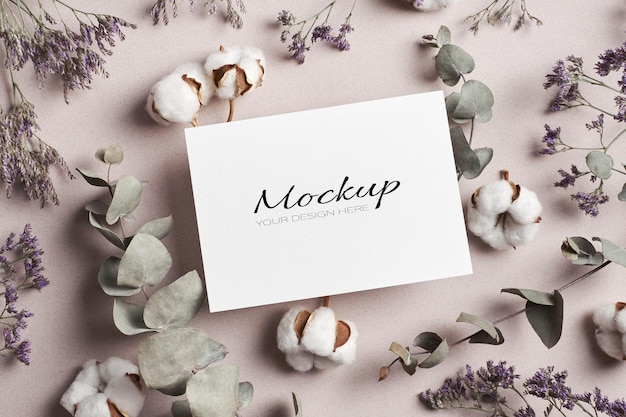 Maquette stationnaire d'invitation ou de carte de voeux avec de l'eucalyptus sec et des fleurs de plantes en pur coton