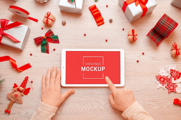 Maquette de tablette entourée de cadeaux et de décorations de noël et du nouvel an