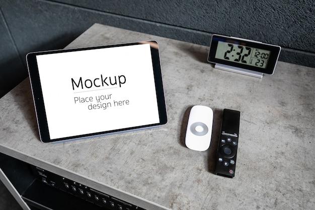 Maquette de tablette avec espace libre à l'intérieur de l'écran. l'appareil est sur la table basse à côté des télécommandes et des montres électroniques