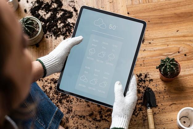 Maquette de tablette numérique psd dans la main d'un jardinier