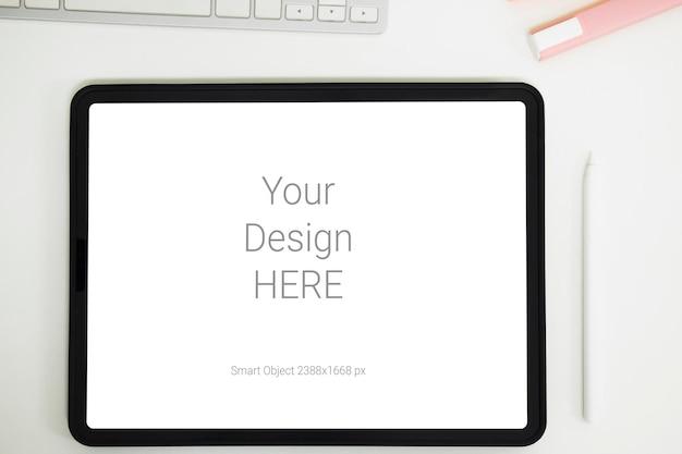 Maquette de tablette numérique sur table de travail de bureau.