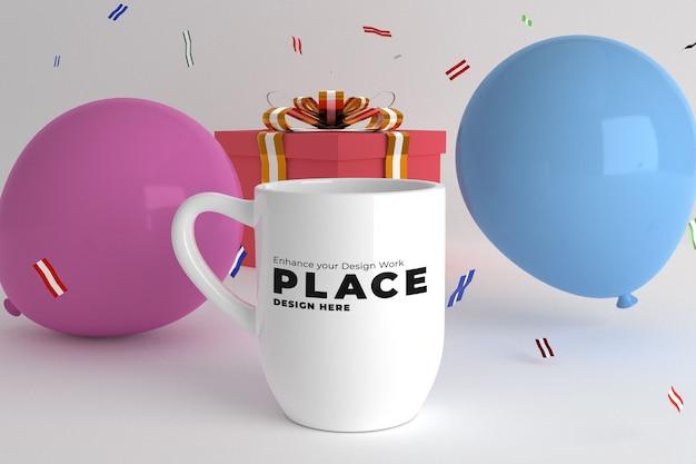 Maquette de tasse avec des confettis d'anniversaire et ballon avec cadeau