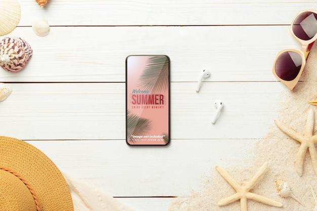 Maquette de téléphone et accessoires de plage sur table en bois blanc.