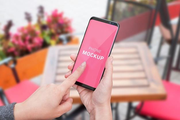 Maquette de téléphone dans les mains de la femme. concept d'écran tactile femme téléphone intelligent. table basse en arrière-plan avec flovers